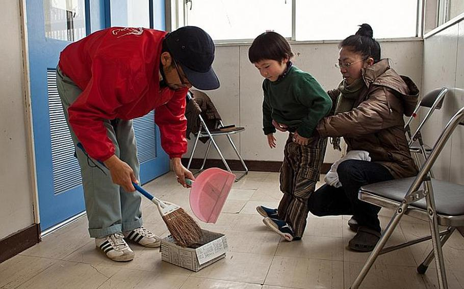 Takeshi Nakagawa and wife Chikako clean up after cutting their son Sota's hair at the Kadonowaki Middle School shelter in Ishinomaki, Japan. The shelter said all displaced residents of the school's classrooms must clear out by the beginning of the new school year on April 21.