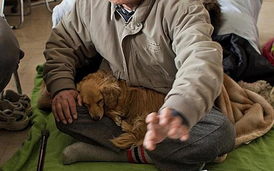 Koichi Matsumoto sits with his dog, Jonko, at the Kadonowaki Middle School shelter in Ishinomaki, Japan. He has applied to live in one of the emergency homes constructed by the government, but said the number of homes is inadequate.