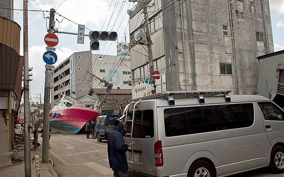 A boat, brought inland during the March 11 tsunami, lies in an Ishinomaki street on Monday.