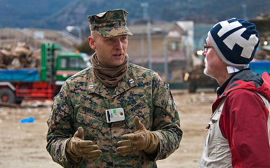 Marine Corps Capt. Robert Gerbracht and Darren Polischuk, a Canadian worker with the Christian relief organization Samaritan's Purse chat after Marines helped deliver boxes of aid that Samaritan's Purse had provided to the displaced residents of the Watanoha Elementary School shelter in Ishinomaki, Japan. The U.S. military has been coordinating with other NGOs to deliver aid.