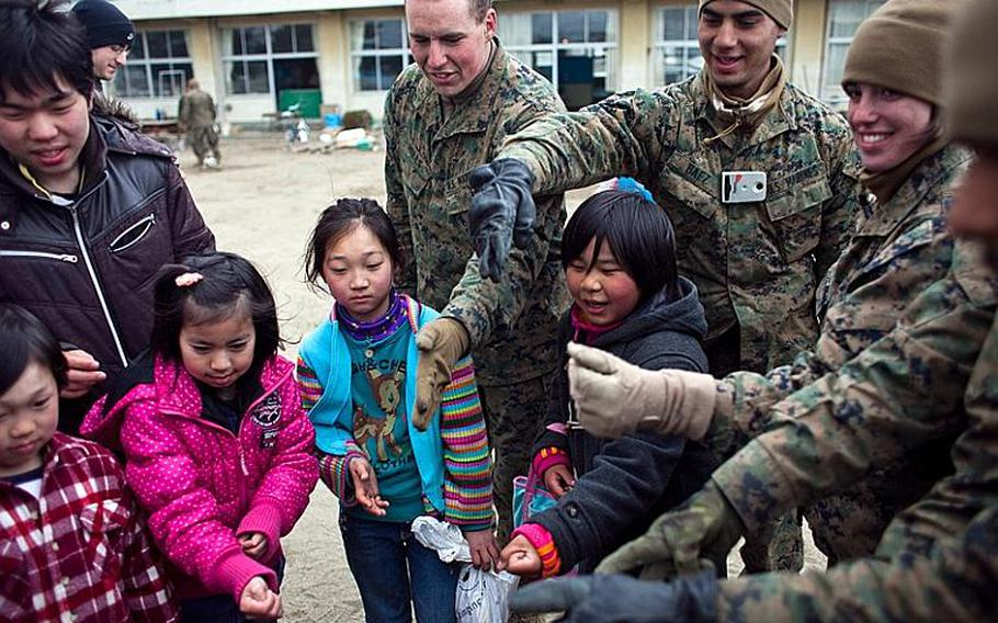 """Marines from Okinawa and Camp Fuji play the game """"rock, paper, scissors"""" with children at the Watanoha Elementary School shelter in Ishinomaki, Japan after assiting to clean up the school grounds as well as to deliver aid provided by the Christian relief organization Samaritan's Purse. The U.S. military has also been coordinating with other NGOs to deliver aid, officials said."""