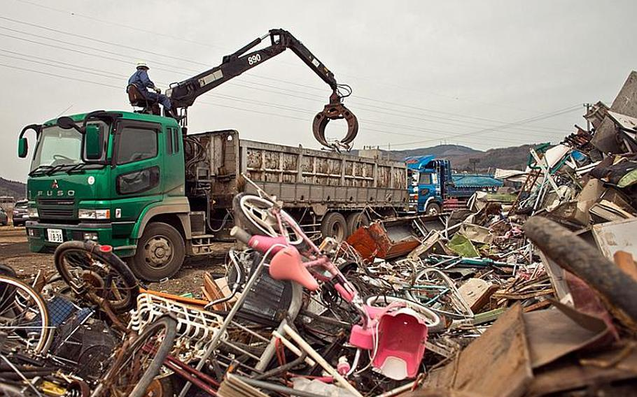 A city worker moves heaps of bikes and other scrap metal into a truck at one of two temporary tsunami-related trash dump sites in Ishinomaki, Japan.