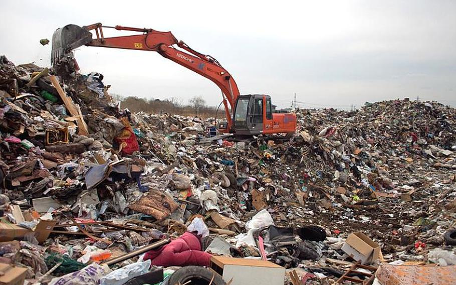 City workers consolidate mounds of trash to create room for more at one of two temporary tsunami-related trash dump sites in Ishinomaki, Japan.