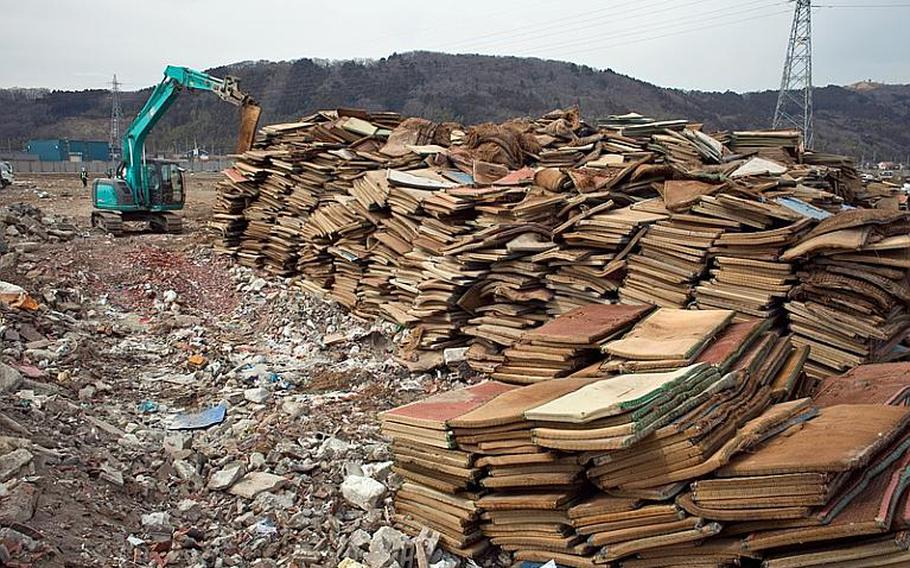A mound of thousands of waterlogged tatami mats sits at the edge of one of two massive dump sites set up to store tsunami-related trash in Ishinomaki, Japan.
