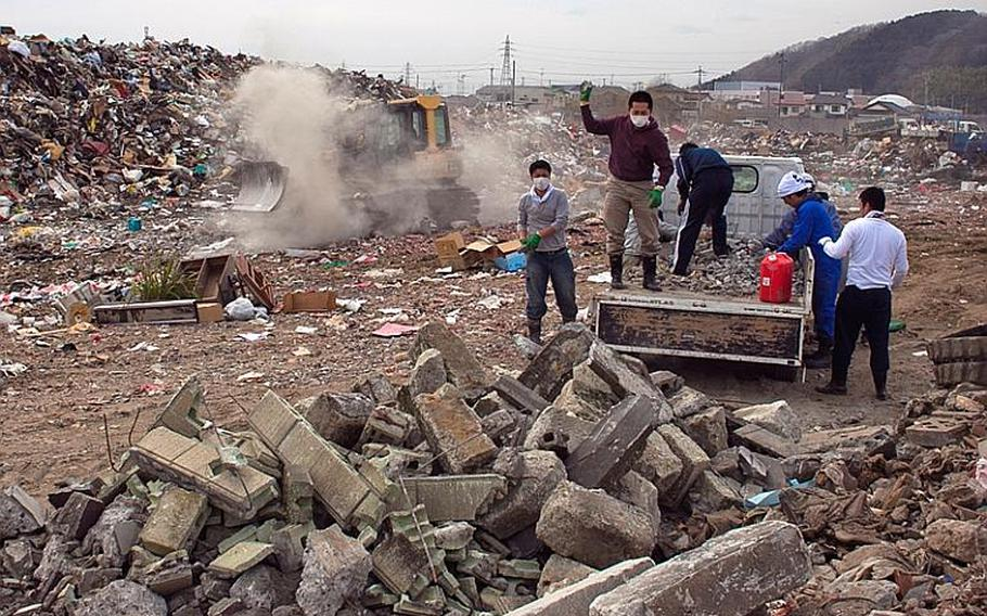 A group of locals empty their truck load of concrete debris as a city worker in a bulldozer moves to consolidate the scattered garbage at one of two massive dump sites set up to store tsunami-related trash in Ishinomaki, Japan.