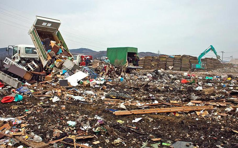 A mound of thousands of waterlogged tatami mats sit in the distance as people bring more garbage and city employees work to consolidate mounds of trash at one of two temporary tsunami-related trash dump sites in Ishinomaki, Japan.