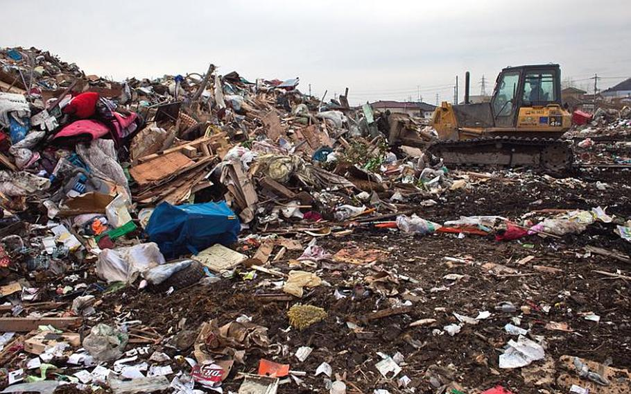 A bulldozer moves to consolidate scattered garbage at one of two massive dump sites set up to store tsunami-related trash in Ishinomaki, Japan.