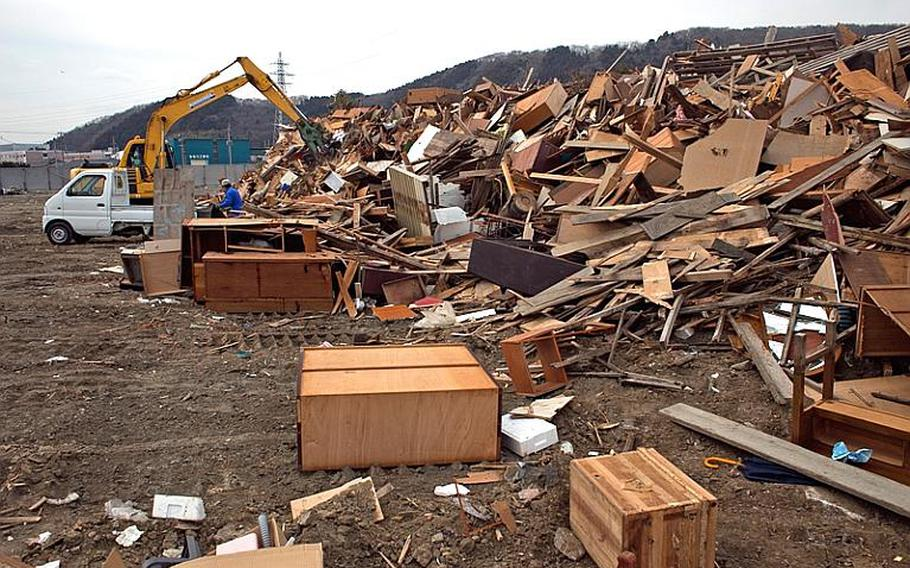 A pile of broken wood sit at one of two tsunami-related trash dump sites in Ishinomaki, Japan.
