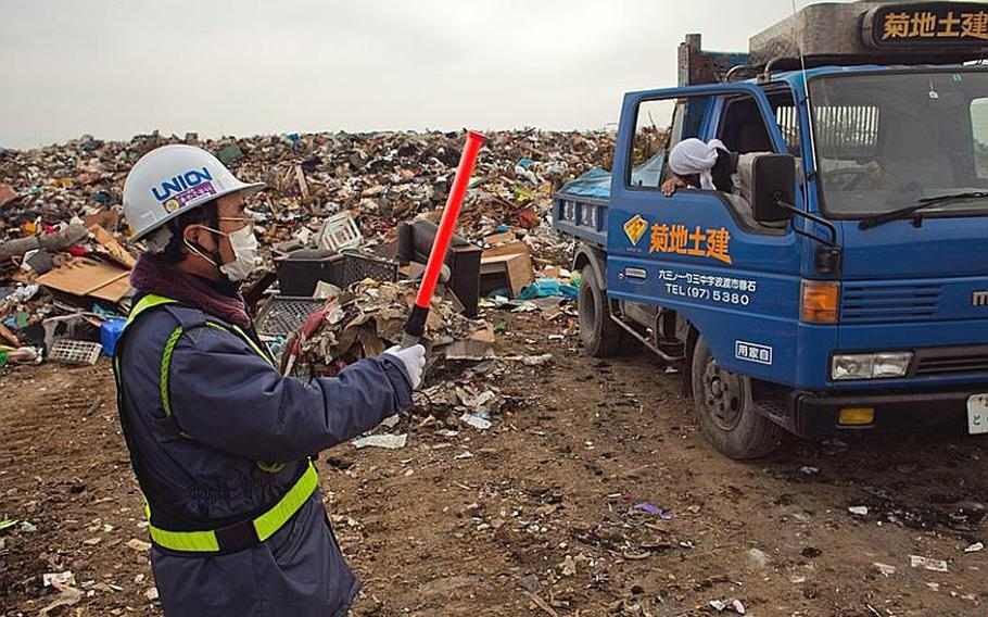 A city worker guides a truck full of tree limbs to the edge of one of two temporary tsunami-related trash dump sites in Ishinomaki, Japan.