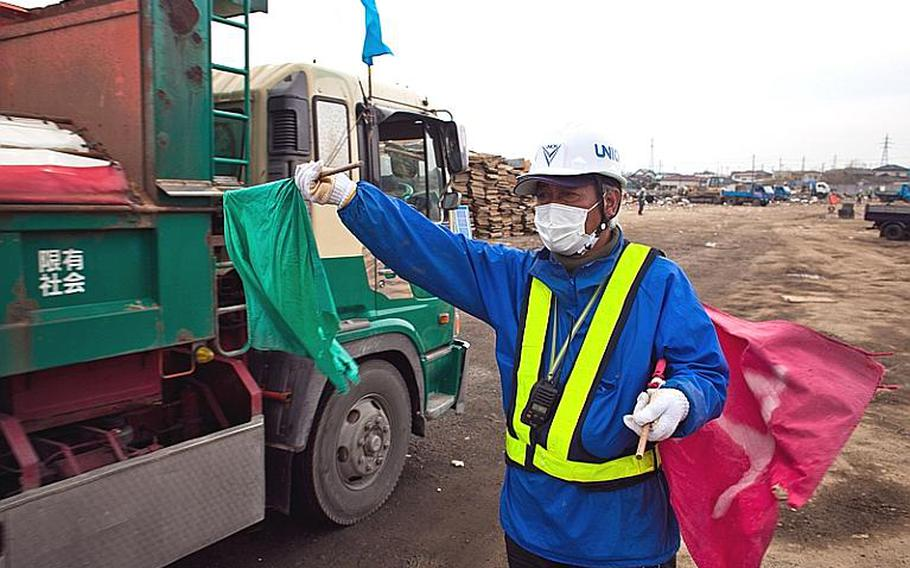 Watanabe Seichi, 55, a city worker, allows passage to a truck full of debris at one of two temporary tsunami-related trash dump sites in Ishinomaki, Japan.
