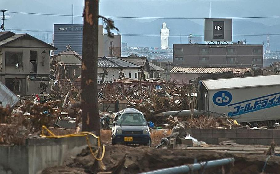 The wreckage from the tsunami devestaed Nagahama Beach area of Sendai sits in contrast to the Sendai Daikannon, which stands in the distant, unscathed Sendai City.