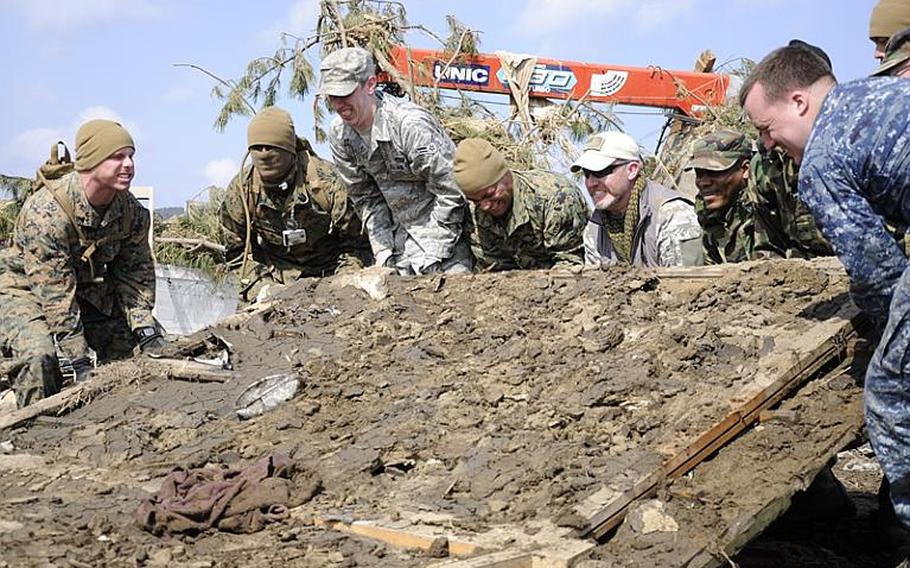 Army veteran Matt Szymanski, fifth from left with the U.S. flag patch on his hat, helps a group of Marines, airmen and sailors attempt to lift a giant piece of debris while helping clean Noda Village, about a two-hour drive from Misawa Air Base, Japan, during a March 29 trip. Szymanski flew to Japan at his own expense to help relief efforts in the Japanese community.