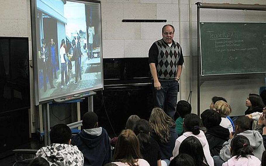 Bill Hunter, standing, shows students at Yokosuka Naval Base in Japan pictures from his recent relief work in the tsunami- and earthquake-ravaged areas near Sendai. Educators at base schools in Japan say they must walk a fine line by teaching students about the disaster, but not increasing their anxieties.