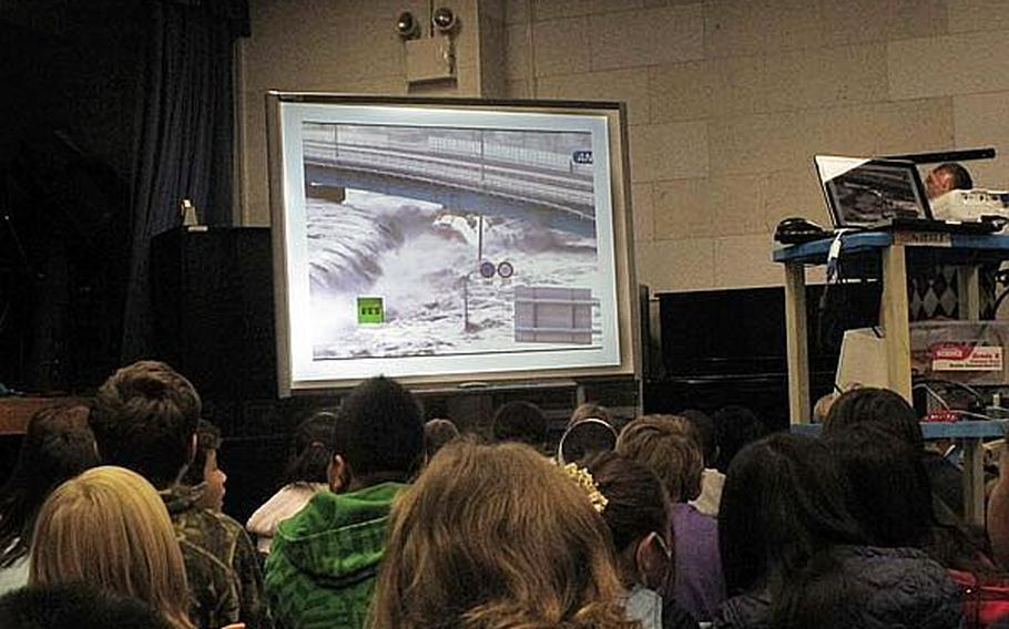 Fourth grade and fifth grade students at Yokosuka Naval Base's Sullivans School in Japan watch video footage of the March 11 tsunami as it overwhelms the nation's coastline. Educators at U.S. military base schools in Japan say they must walk a fine line by teaching students about the disaster, but not increasing their anxieties.
