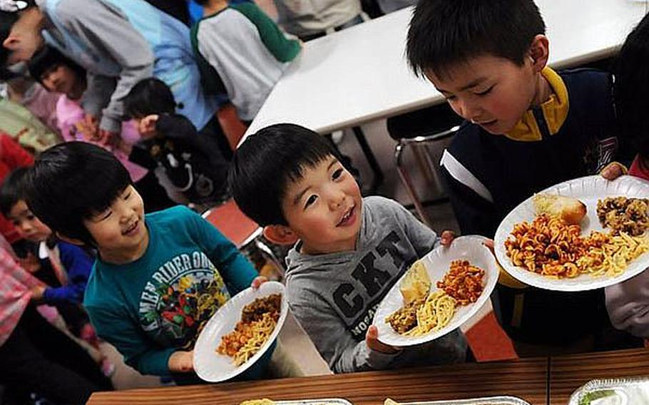 Children at Bikou-en Children's Care House wait in line for a home-cooked meal delivered March 27 by sailors from Naval Air Facility Misawa.