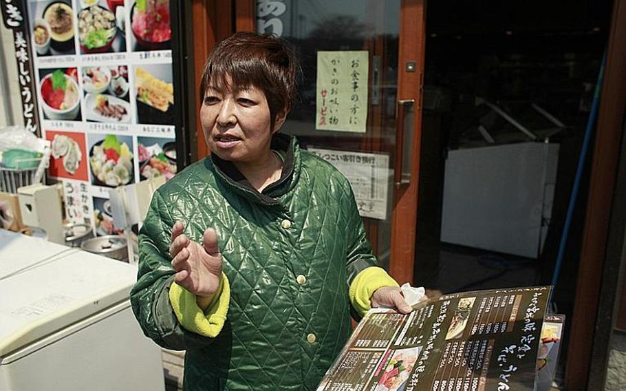 Junko Okumi, 51, stands in front of her sashimi restaurant in Matsushima. She said she expects local seafood to be in short supply when she reopens.