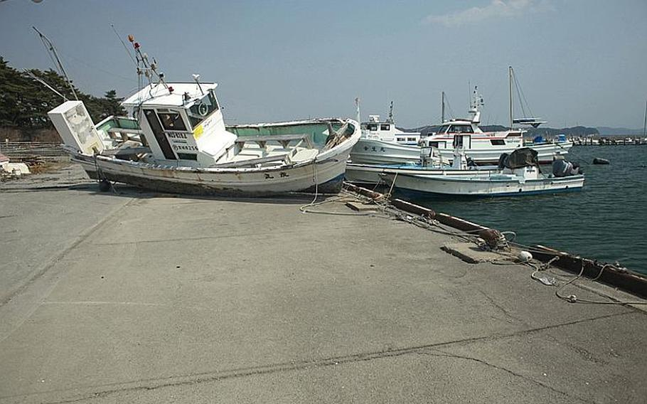 A fishing boat, washed ashore during the March 11 tsunami, sits on a pier at a harbor in Matsushima, Japan.