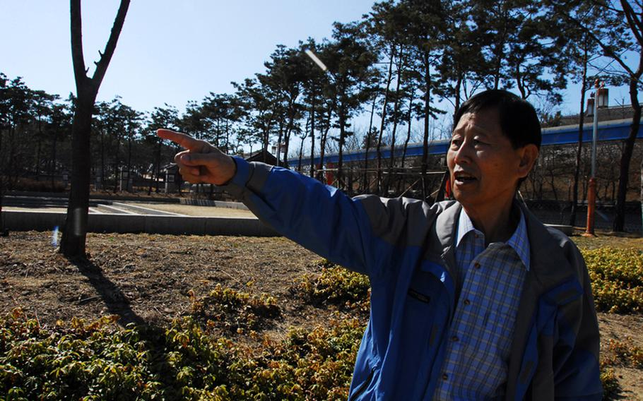 """Jang Seok Ju, 73, points to the area where his family used to live in what was then a village on Wolmi Island. The area, bombed by U.S. troops in the days before the Sept. 15, 1950, Incheon Landing, is now a park. """"My heart is broken,"""" he said."""