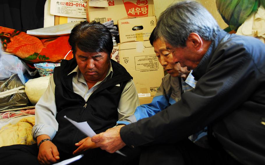 (from left to right) Jeong Ji-eun, Jang Seok Ju and Jon Chon-bong look at old aerial photographs of Wolmi Island, where they lived before the U.S. bombed the island in September 1950 to rid it of North Korean troops. The men are part of a group of former Wolmi Island residents suing the city of Incheon, South Korea, the United States and the United Nations for damages caused to their families' property during the bombings.