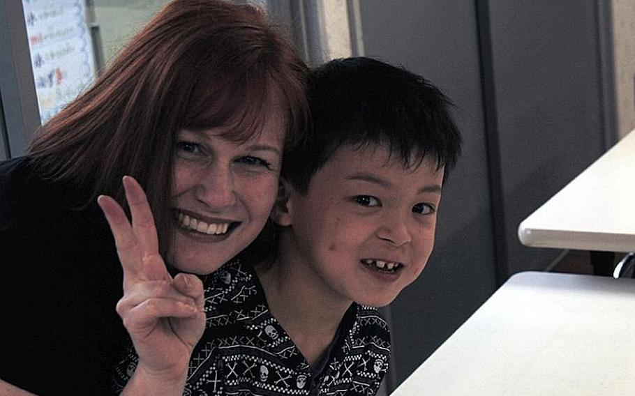 Gemini Sanford poses with one of the orphans at the Bikou-en Children's Care House in Shichinohe, Japan. Sanford has spearheaded efforts from Naval Air Facility Misawa, Japan, to bring food and supplies to the children following a March 11 earthquake.