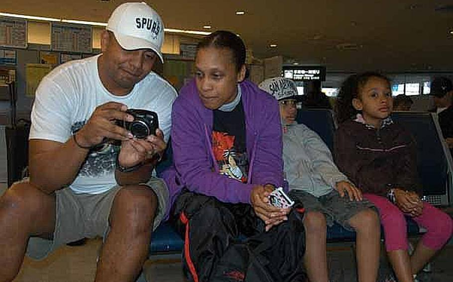 Miguel Rodriguez, 40, left, shows videos of a San Antonio Spurs basketball game to his wife, Army Spc. Tina Johnson, 37, while their daughter, Leilani, 7, and son, Nehemiah, 10, wait for a bus at Narita Airport, Japan, on Friday. Thousands of family members, who left Japan following the March 11 earthquake are now returning.