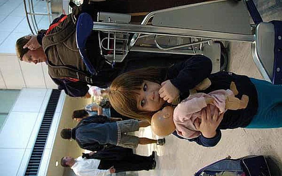 Emily Dibble, 2, clutches her doll as she and mother Candace waits for a bus to Yokosuka Naval Base. The Dibbles were among thousands of family members who left Japan following the March 11 earthquake and are now returning now that the Defense Department is ending its voluntary departure program.