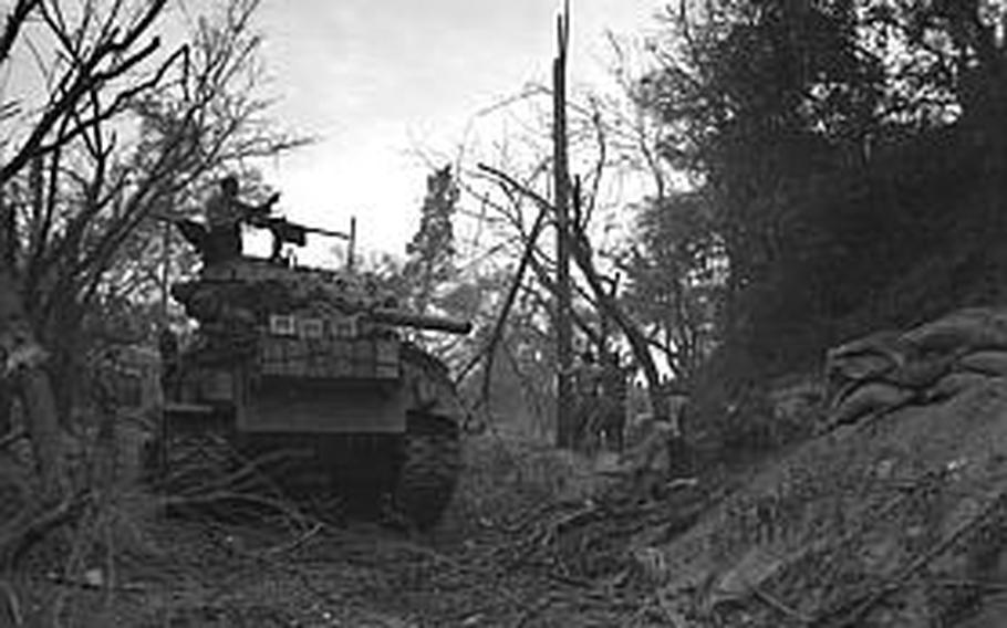 Tank-led U.S. Marines accept the surrender of the enemy on Wolmi Island as the tank commander points out another pillbox.