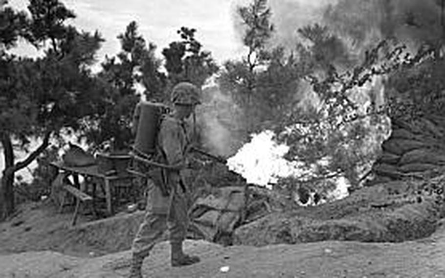 A U.S. Marine uses a flame thrower to burn out an enemy position on Wolmi Island, gateway to Inchon.
