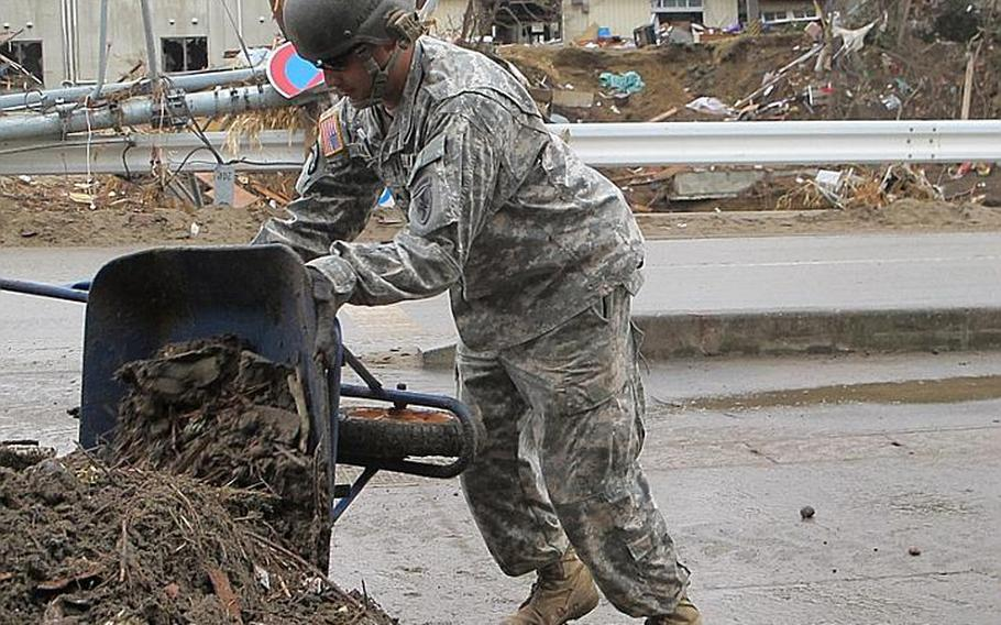 Cpl. Jorge Alaniz dumps another pile of dirt shoveled from Nobiru train station during one of dozens of wheelbarrow trips he made Friday. A 42-soldier combined unit from both Camp Zama and Okinawa completed the cleanup at Nobiru and had finished clearing another station by Monday.
