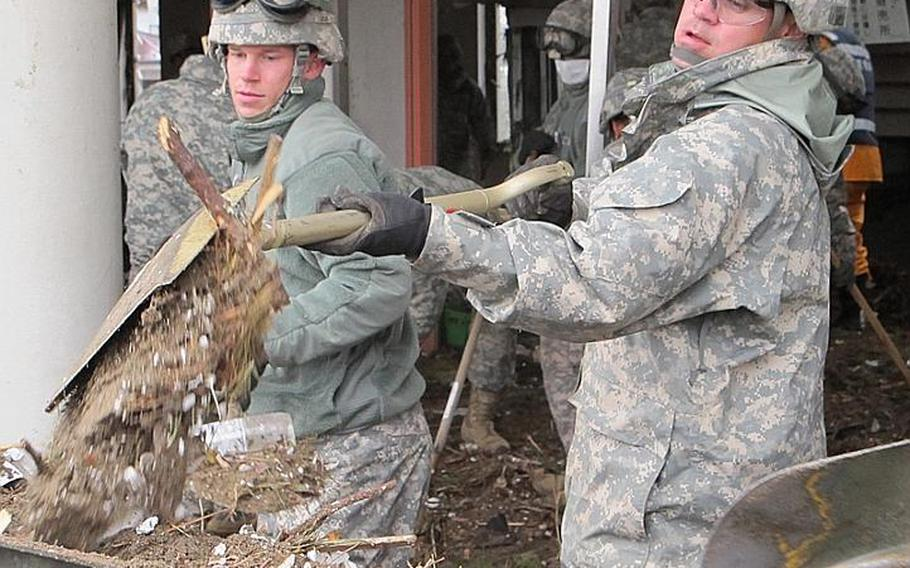 Spc. Timothy Jones, left, and Spc. Ivan Santos shovel dirt and debris while clearing out Nobiru train station on Friday, in Japan's tsunami-battered northeast. A 42-soldier combined unit from both Camp Zama and Okinawa completed the cleanup at Nobiru and had finished clearing another station by Monday.