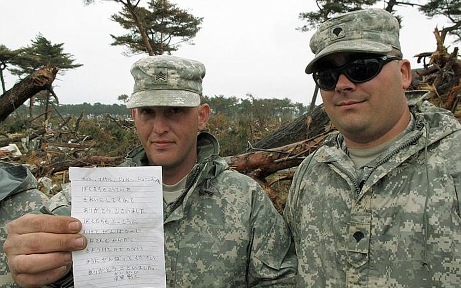 Sgt. Joshua Mason, left, displays a thank-you note he received after he and his unit of 42 soldiers cleaned up a school in tsunami-ravaged northeast Japan recently. The appreciation has meant a lot to soldiers like Mason, who have been clearing train stations of muck and debris since Thursday.