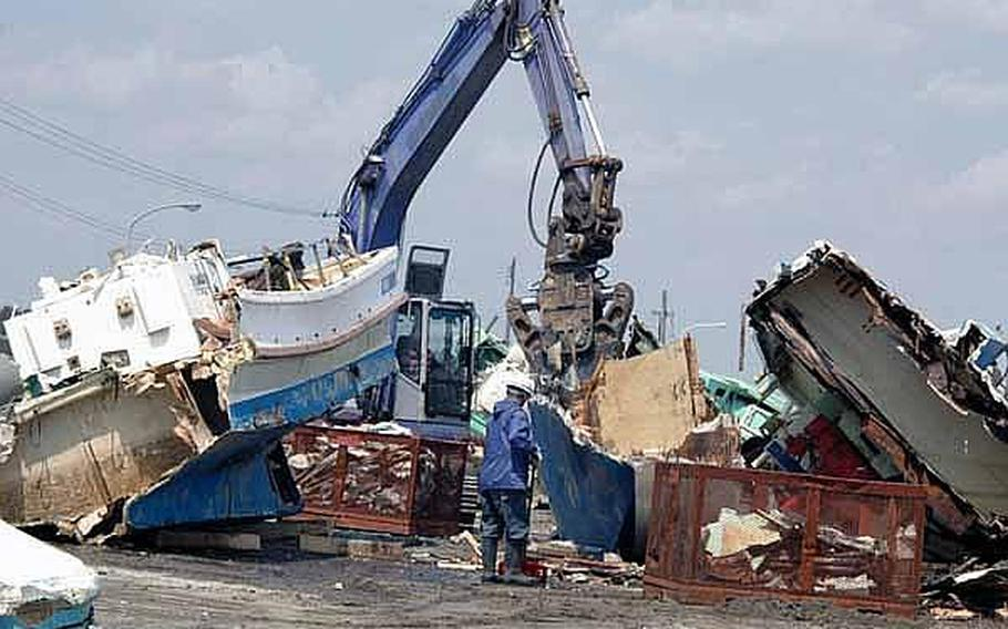 Japanese workers use heavy machinery Tuesday at the Misawa City port to smash apart boats that were washed ashore in a March 11 tsunami. Officials are trying to get the port ready for a mid-June squid harvest, which is vital to the local economy.