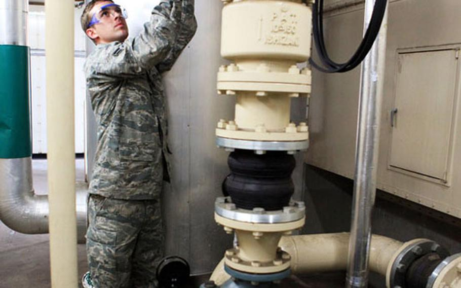 Airman 1st Class Matthew Ewing, 374th Civil Engineer Squadron, works on the chill water valve for an air conditioning unit to help with energy saving measures Friday on Yokota Air Base, Japan.