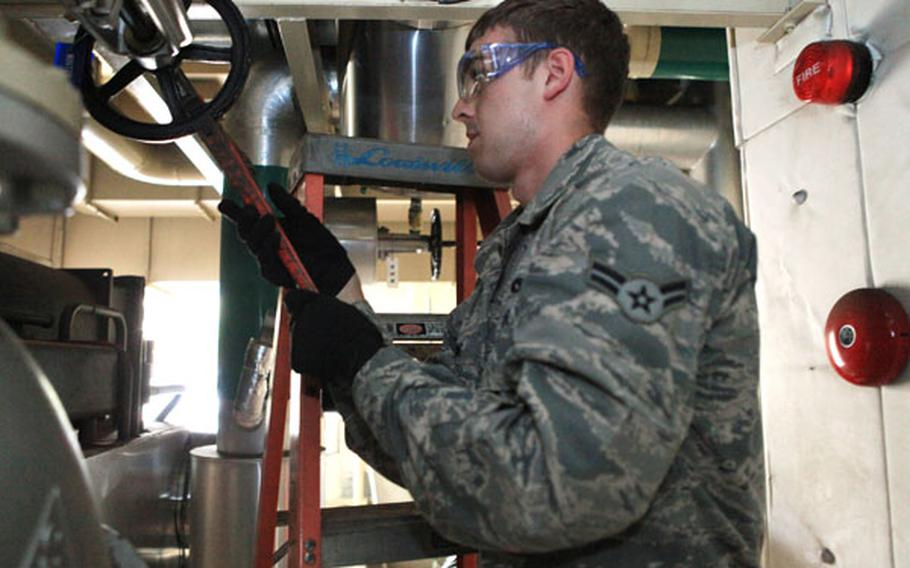 Airman 1st Class Matthew Ewing, a heating and ventilation technician from the 374th Civil Engineer Squadron, works on the chill water valve for an air conditioning unit to help with energy saving measures Friday on Yokota Air Base, Japan.