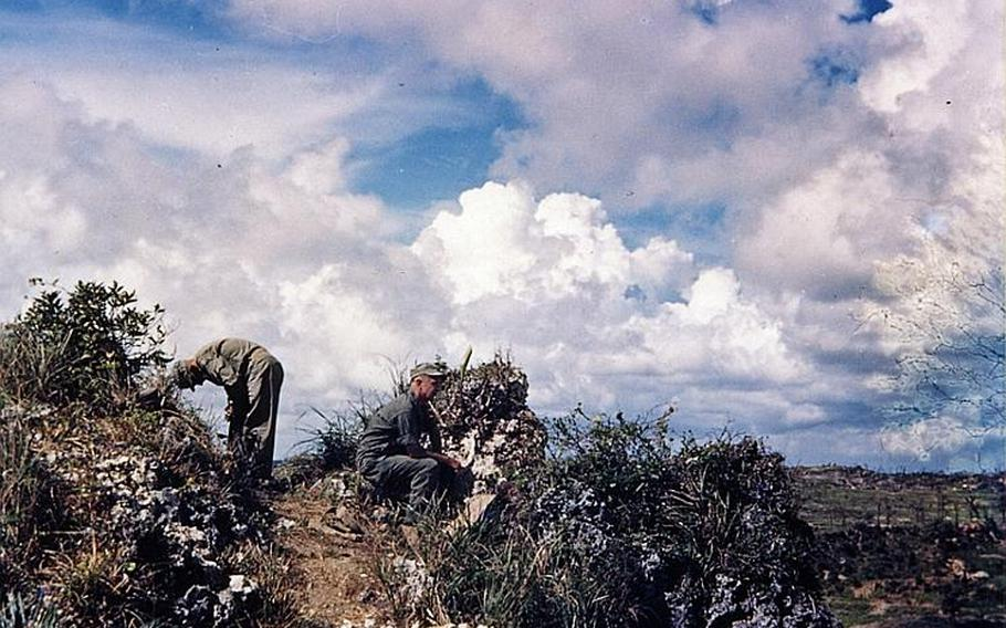 Two servicemembers give a safety check of a path from atop a ridge in the southwestern tip of Okinawa for a visit of Army Lt Gen. Simon B. Buckner, Jr., who led Army and Marine troops in the Battle of Okinawa. Shortly after taking this photo, Buckner was killed when fragments of an artillery shell struck him in June 18, 1945, five days before the battle ended on the island.