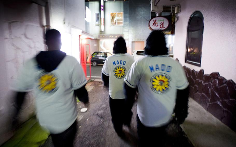 Members of Maintenance Monkeys Against Drunk Driving walk through an alley in downtown Misawa in late 2009 to offer free rides home in an effort to curb drinking and driving in the local community.