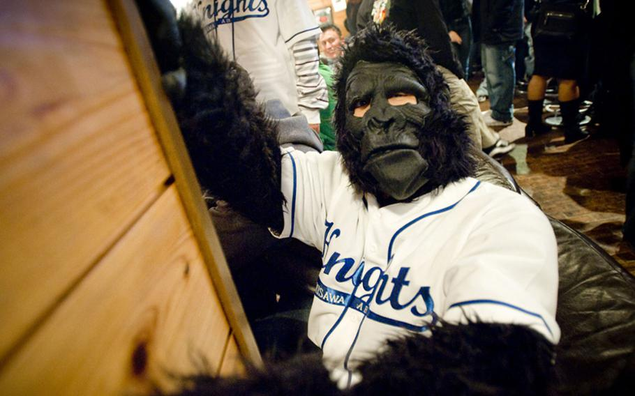A member of the Maintenance Monkeys Against Drunk Driving hangs off the wall of a downtown Misawa bar in this November 2009 photo. The group uses the costumes to gain attention to its volunteer ride program to stop base members from drinking and driving.