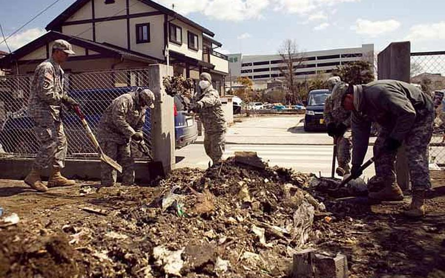 Soldiers from Logistics Task Force 35, shovel debris from a school yard in Ishinomaki, Japan, following the March 11 earthquake and tsunami. Military health officials say that air, water and soil samples tested in the region in April did not contain dangerous levels of toxins or radiation.