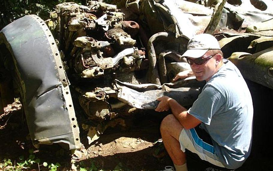 Pat Ranfranz  crouches next to the wreckage from an old U.S. Navy FSF shipboard fighter plane he helped to discover in 2006 on  Yap Island during his search ifor the crash site of his uncle's long lost  B-24J bomber.