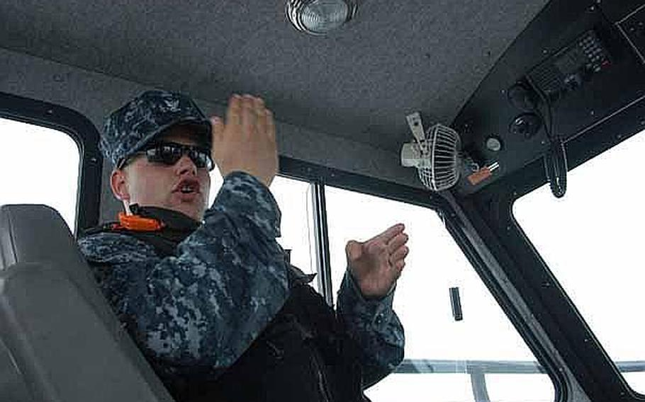 Petty Officer 3rd Class Richard Wood offers some guidance to Seaman Apprentice Corrine Roberts, who is new to Sasebo Naval Base and harbor security. The harbor security team works around the clock to keep U.S. Navy assets in the area safe.