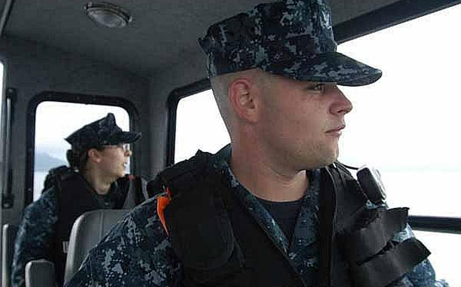 Seaman Apprentice Corrine Roberts, left, and Petty Officer 3rd Class Richard Wood keep a lookout for any lurking dangers as part of the harbor security team at Sasebo Naval Base, Japan.