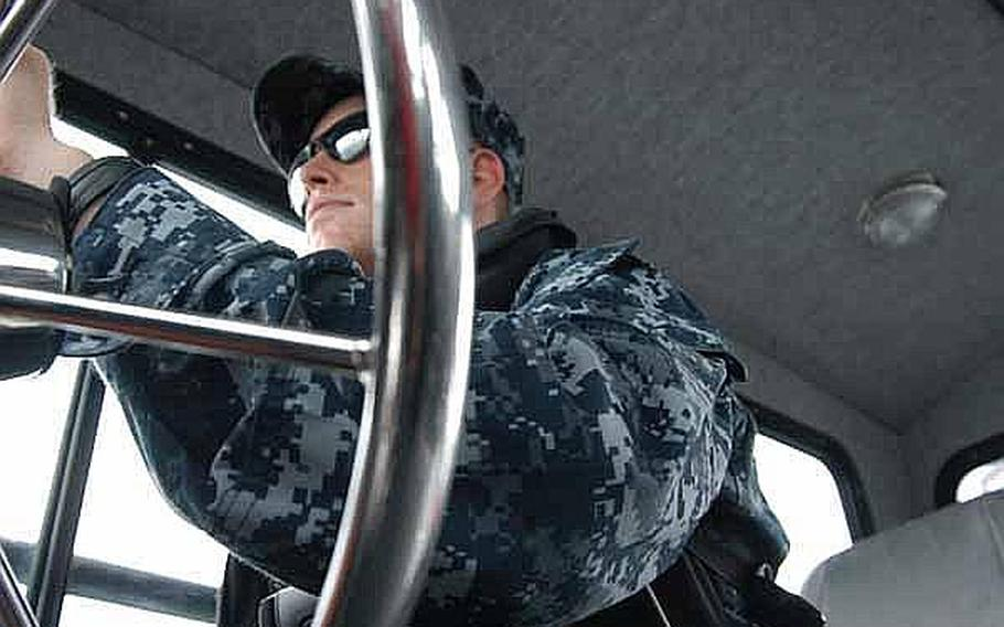Petty Officer 2nd Class Ryan Blazer is at the helm on a mid-June patrol of the harbor near Sasebo Naval Base, Japan.