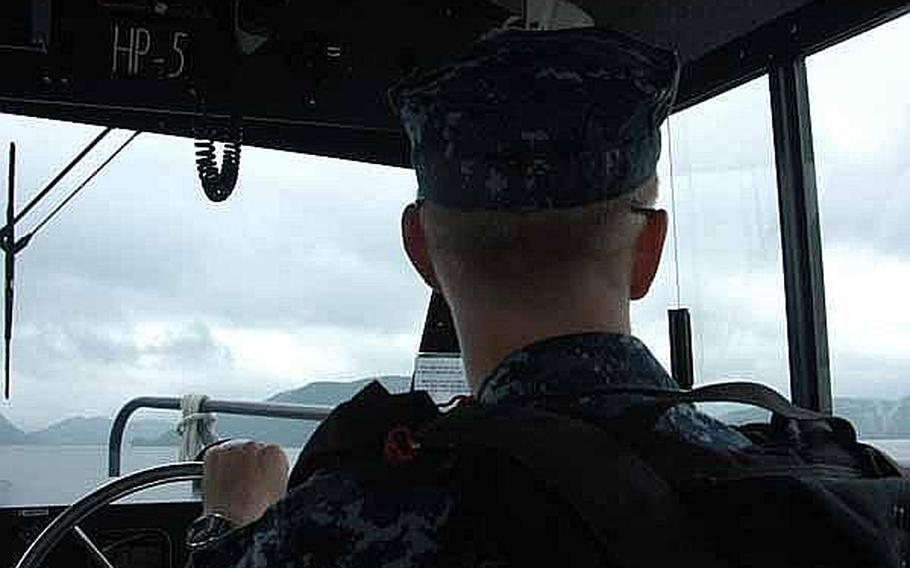 Petty Officer 2nd Class Ryan Blazer surveys his surroundings while on a mid-June patrol of the harbor near Sasebo Naval Base, Japan. Blazer is part of the Sasebo harbor security team charged with keep U.S. Navy assets in the area safe.
