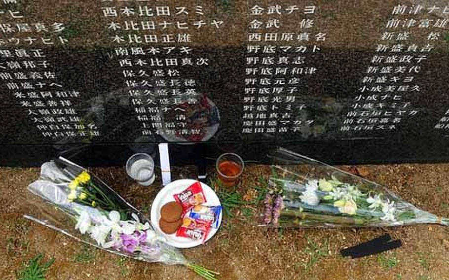 Food, drinks, and flowers rest at the base of one of the many granite walls etched with the names of all who died during the Battle of Okinawa.