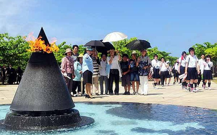 A tour guide explains to listeners about the 'Flame of Peace,' memorial, which is at the end of the 1,200 granite walls bearing the names of 240,000 military and civilians who died during the Battle of Okinawa. The top of the metal cone is lit at all times and water tumbles from the base of the cone and fills a circular pool with a map of the Pacific at the bottom.