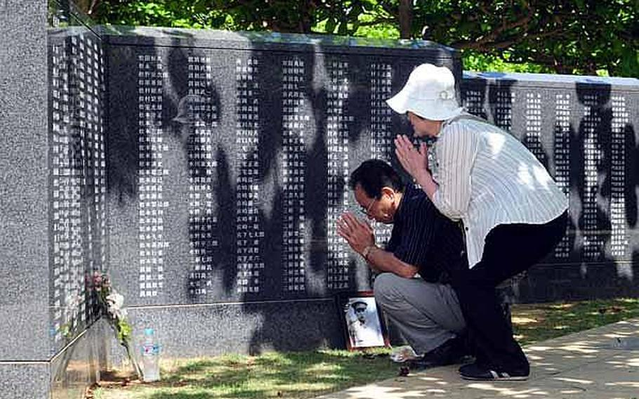 A man and woman bow their heads and offer a few minutes of prayer for a loved one who died in the Battle of Okinawa.