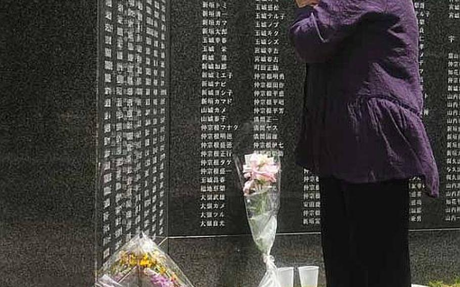 A woman offers prayers at Peace Prayer Park on Wednesday, the anniversary of the end of the Battle of Okinawa. More than 240,000 names are inscribed on the granite walls, memorializing all those that lost their lives.