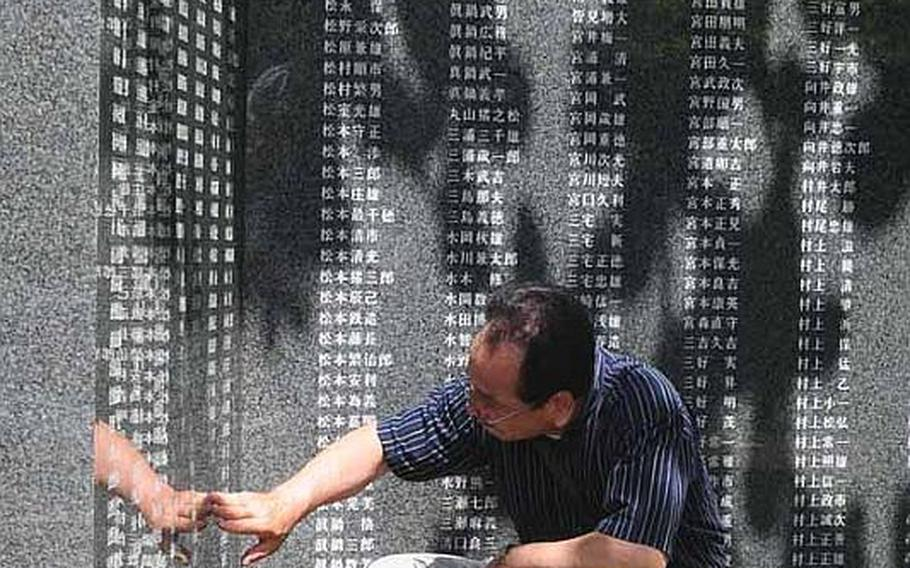 A man touches name of a loved one at a memorial of the Battle of Okiwana. There are more than 240,000 names etched into the large granite walls.