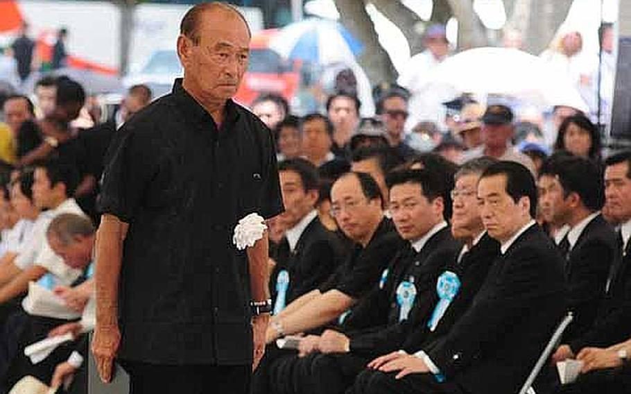 Okinawa Governor Hirokazu Nakaima finishes his bow to government officials after placing a chrysanthemum on a table during the Battle of Okinawa memorial service Thursday at the Peace Prayer Park in Itoman.