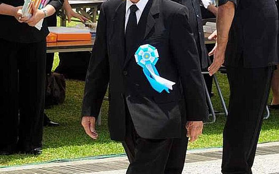 Takeo Nishioka, Speaker of the House of Councilors walks to his chair Thursday for the commencement of the Battle of Okinawa memorial service at Peace Prayer Park in Itoman.